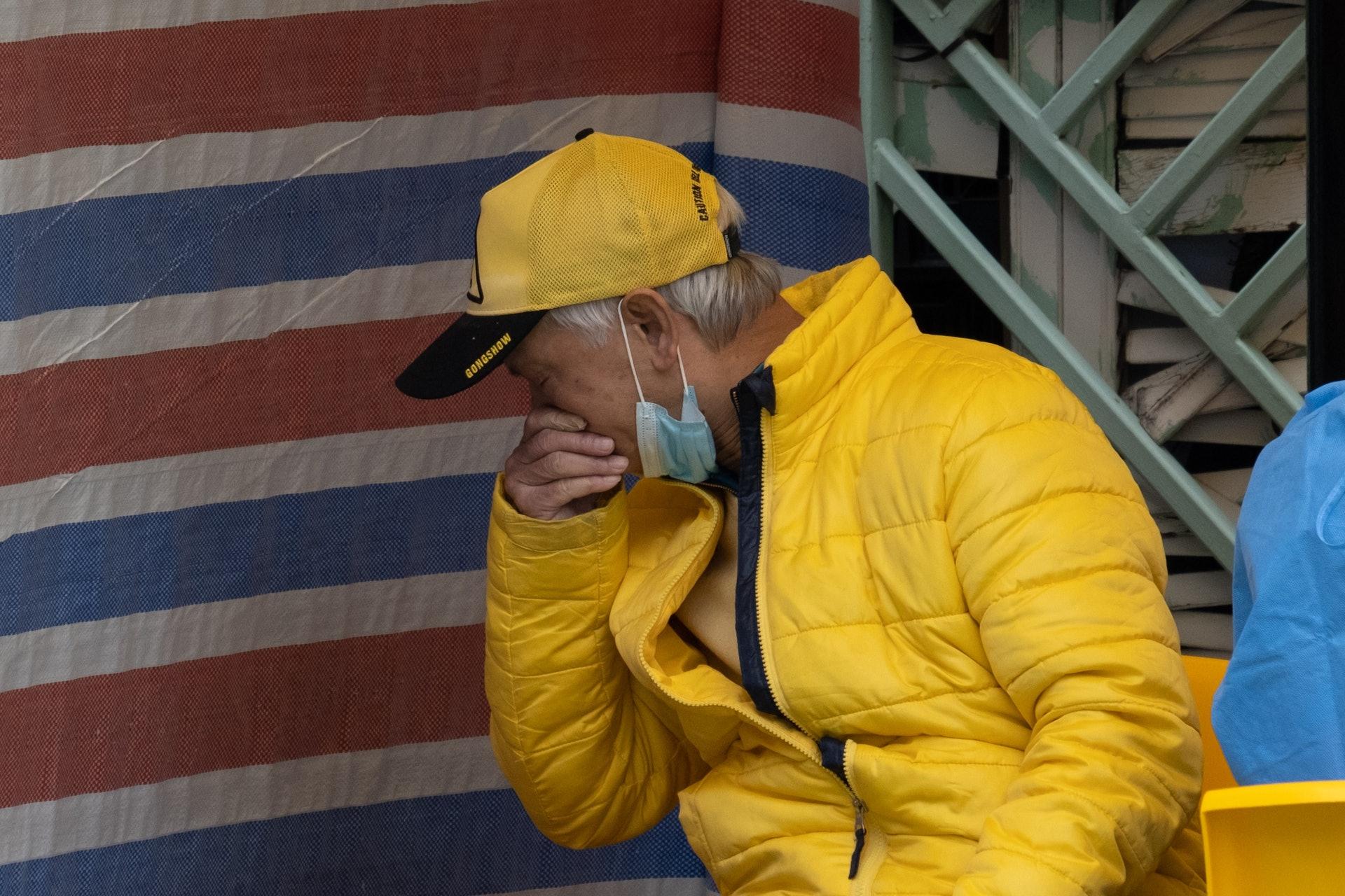 沙田乙明邨明恩樓爆疫,當局在乙明邨籃球場設立流動採樣站,有長者接受檢測後,感到不適打噴嚏。(梁鵬威攝)