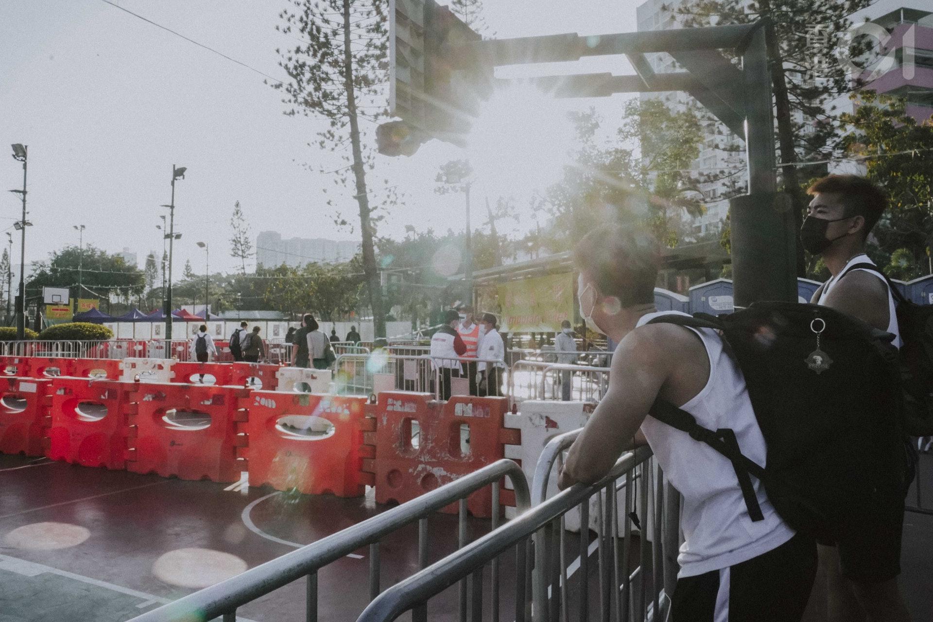 看著市民經過籃球場,走入足球場買花。(袁志浩攝)