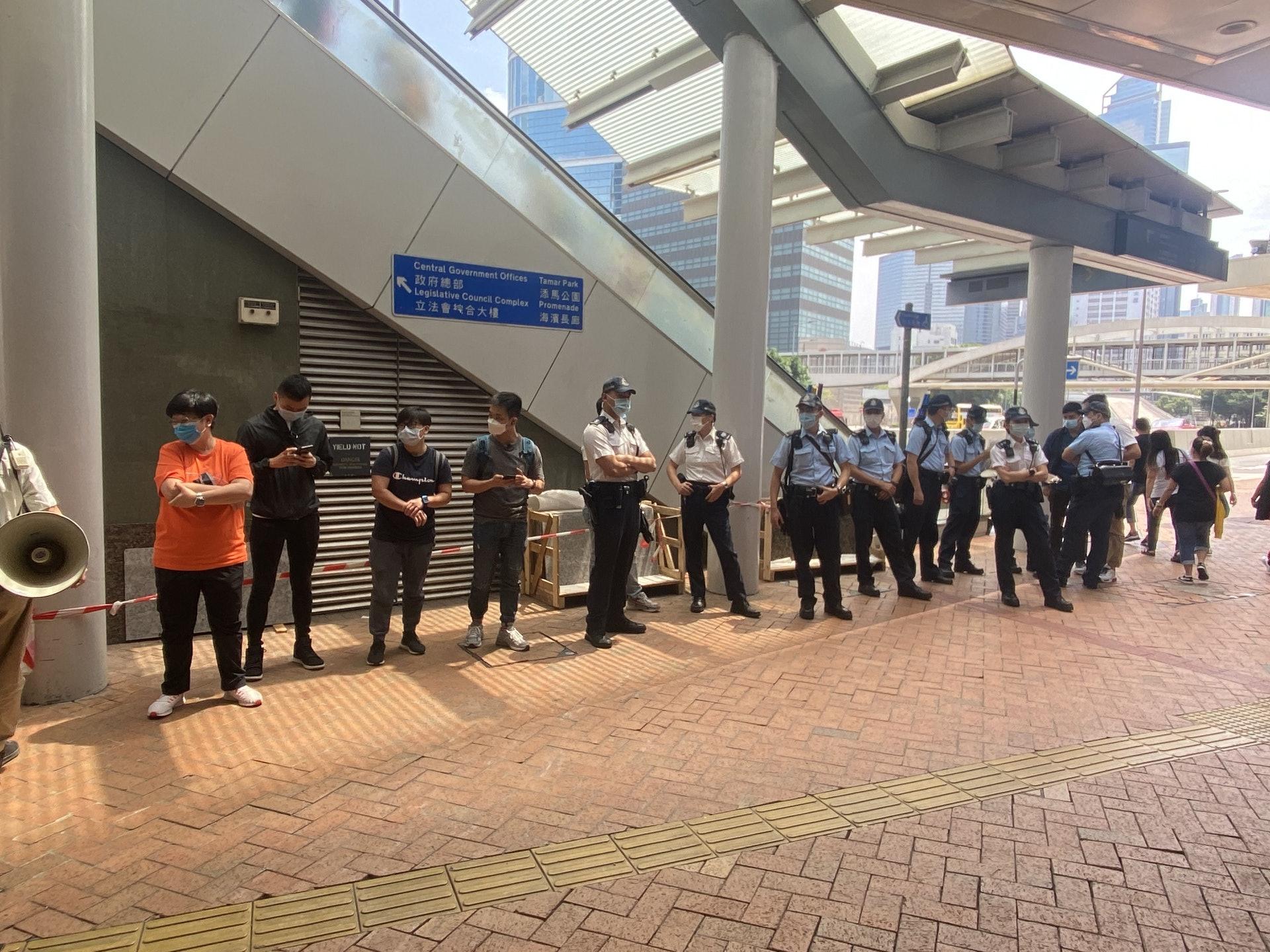 十數名警察戒備,旗袋裝有警告違國安法的紫旗。(鍾妍攝)