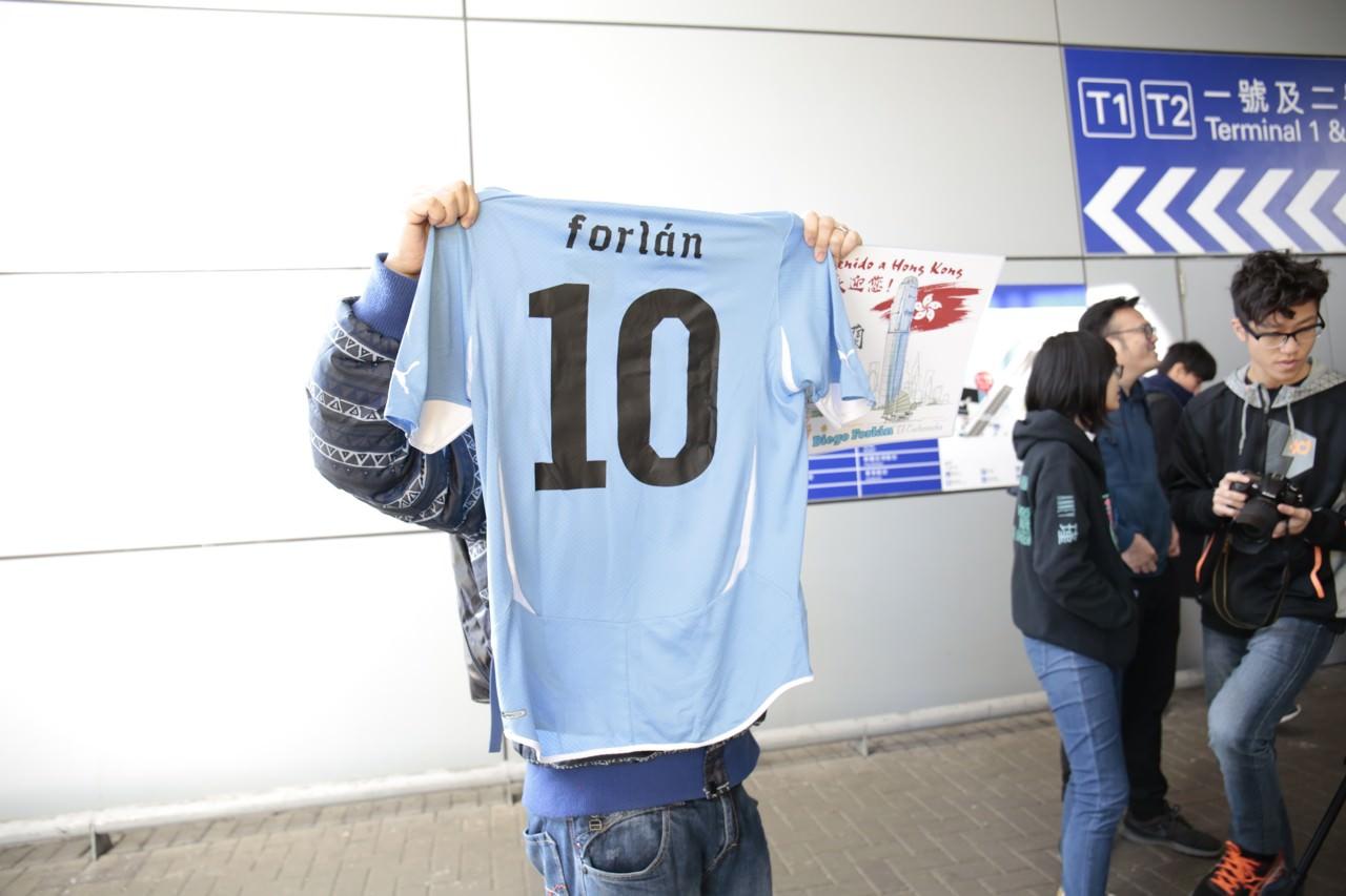 科�m抵港前,已有大批球迷在球�鎏�e通道守候,其中一名球迷高�e科�m代表�趵�圭��家��r穿著的10�球衣。(高�琦�z)