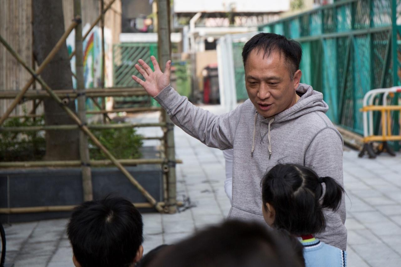 約30名來自小一至小三的同學們先分組,專心聆聽師傅大哥講解是日任務是什麼。(張浩維攝)