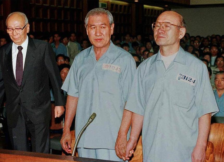 兩名韓國前總統全斗煥(右)與盧泰愚(中)在法庭上手牽着手,一同接受審訊。(Getty Images)