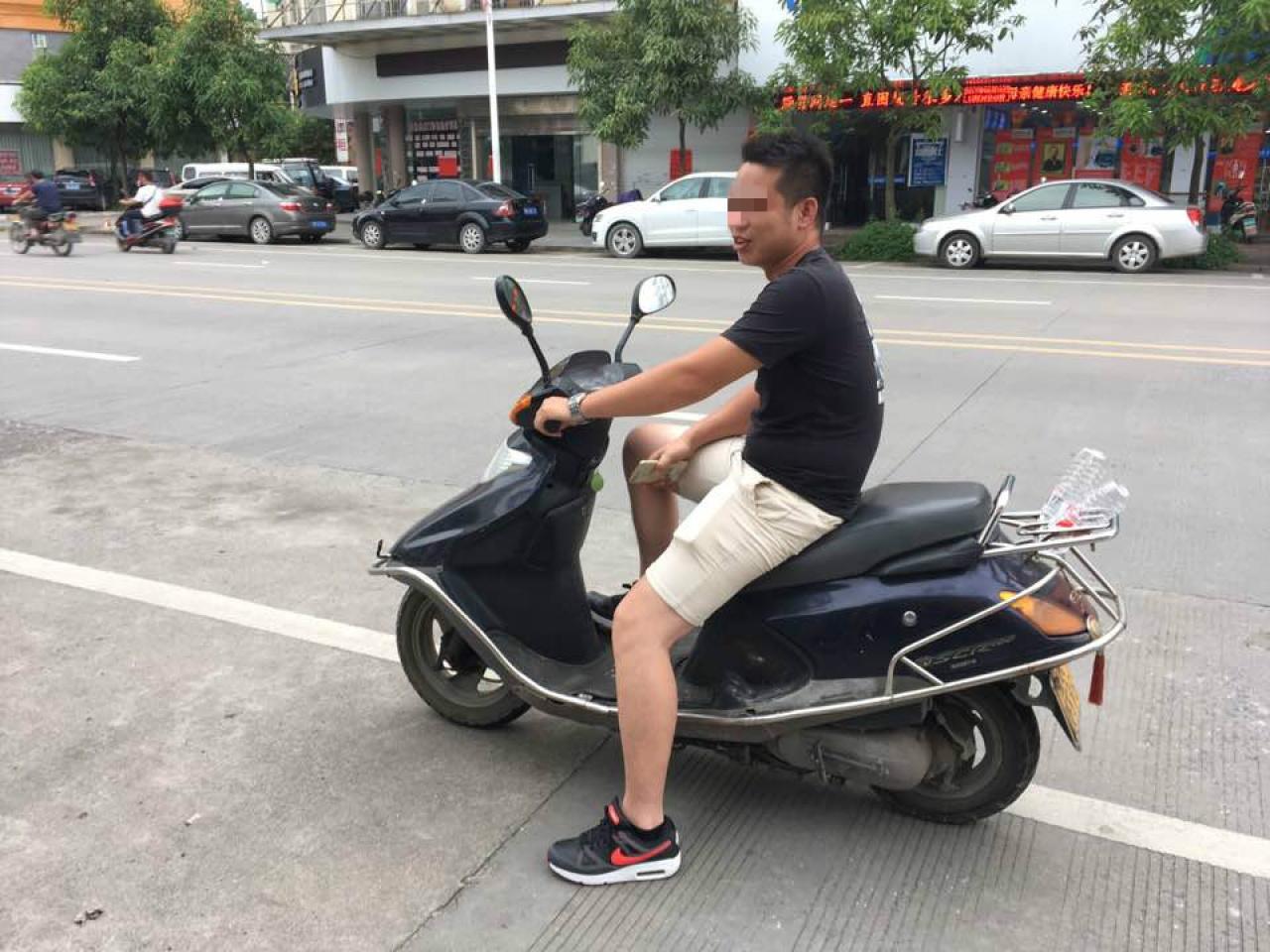 2017年玉林狗肉節前夕,騎車便衣人員態度從容,甚至能讓記者擺拍。(李俊杰攝)